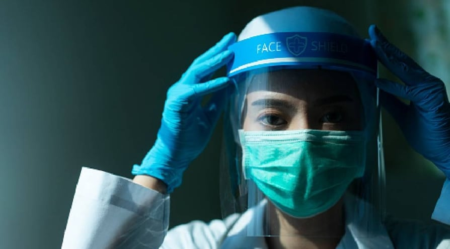Closeup Asian female Doctor wearing face shield and PPE suit and praying for stop Coronavirus outbreak or Covid-19, Concept of Covid-19 quarantine - stock photo