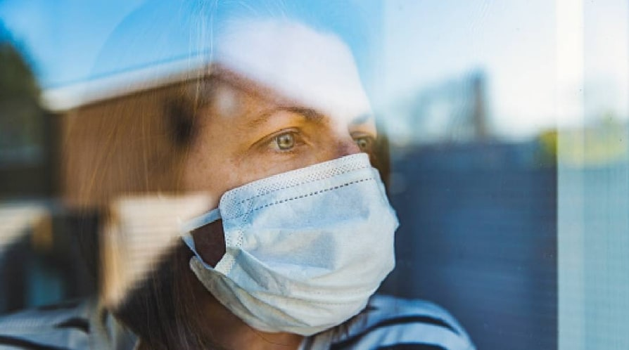 Woman in mask looking through window - stock photo