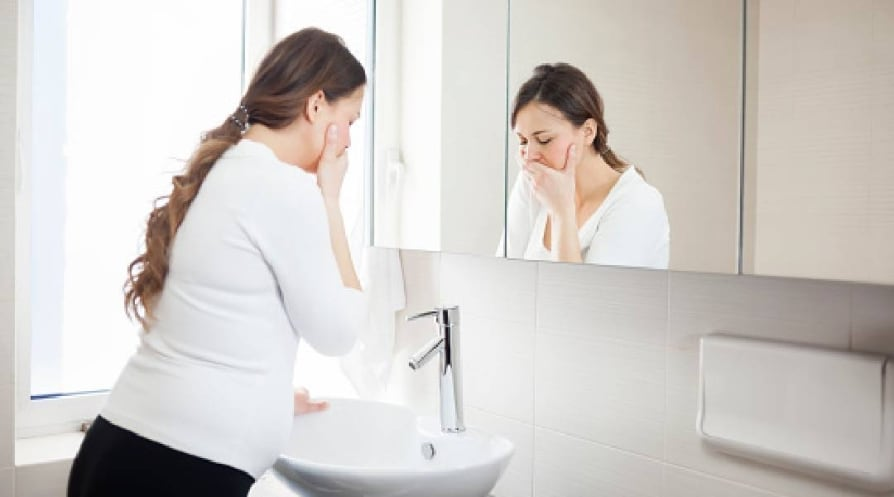 Morning sickness - stock photo Young Pregnant Woman Suffering With Morning Sickness In Bathroom
