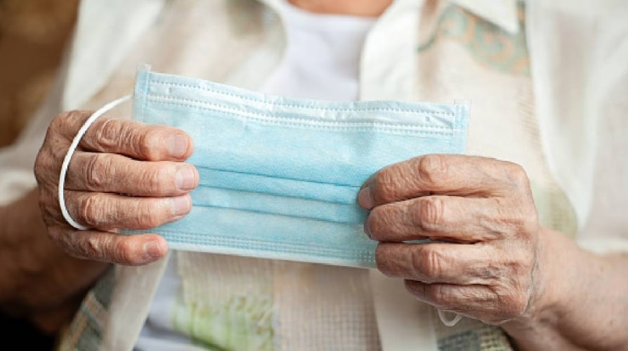 Old woman holds medical mask in hands, blank table - stock photo