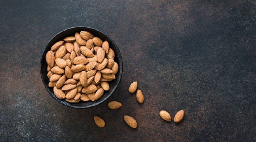 Almonds in bowl on background - stock photo