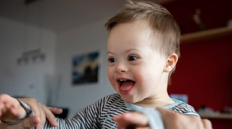 Happy Boy With Down Syndrome Held By Father At Home - stock photo